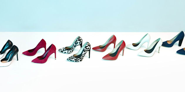 A line of pairs of women's high heeled shoes.  Studio shot.