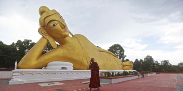 A Bangladeshi Buddhist monk walks in front of a Buddha statue at one of the rebuilt Buddhist temples in Ramu, in the coastal district of Cox's Bazar, Bangladesh, Wednesday, Sept. 11, 2013. The Bangladesh government has rebuilt a total of 19 Buddhist temple that were torched an overnight attack by Muslims last year. Buddhists make up less than 1 percent of Muslim-majority Bangladesh's 150 million people. (AP Photo/A.M.Ahad)