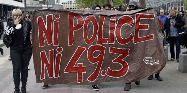 Protesters hold a banner reading 'No police, nor 49.3' on May 14, 2016 in Rennes, western France, during a demonstration against the government's planned labour law reforms.