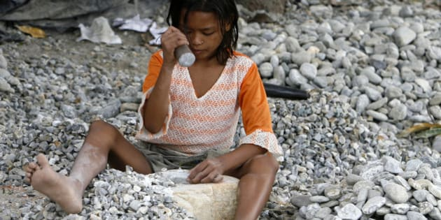 Nine-year old Ganga Burman, a child labourer, breaks stones on the banks of river Balason on the outskirts of the eastern Indian city of Siliguri June 12, 2009.  The International Labour Organization (ILO) celebrates World Day Against Child Labour on Friday.  REUTERS/Rupak De Chowdhuri (INDIA SOCIETY)