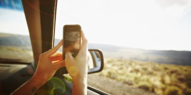 Woman riding in front seat of car driving through desert taking digital photo with smartphone