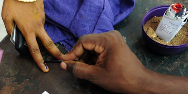 An Indian electoral official marks the finger of a voter with ink at a polling station in Chennai on May 16, 2016, during voting in state assembly elections in the southern Indian state of Tamil Nadu.