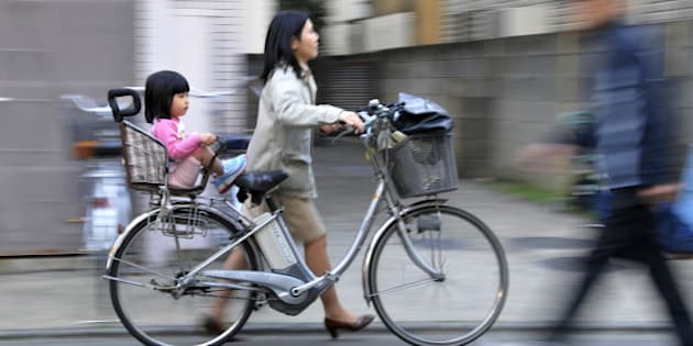 JAPAN-EDUCATION-SOCIETY-CHILDREN, FEATURE, BY MIWA SUZUKI A mother pushes her bicycle carrying her daughter she picked up from a nursery school in Tokyo on March 19, 2010. Parents known as 'monsters' for their aberrant demands have been pushing nursery and school workers over the edge, so much so that some teachers killed themselves, in a nation with one of the world's lowest birthrates.  AFP PHOTO / Yoshikazu TSUNO (Photo credit should read YOSHIKAZU TSUNO/AFP/Getty Images)