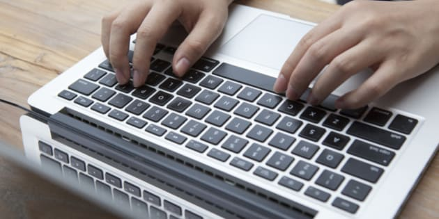 Two hands typing on a keyboard of a laptop computer.