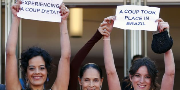"Cast members Maeve Jinkings (L) and Sonia Braga (C) hold placards to protest against the impeachment of suspended Brazilian President Dilma Rousseff as they arrive on the red carpet for the screening of the film ""Aquarius"" in competition at the 69th Cannes Film Festival in Cannes, France, May 17, 2016.   REUTERS/Yves Herman"