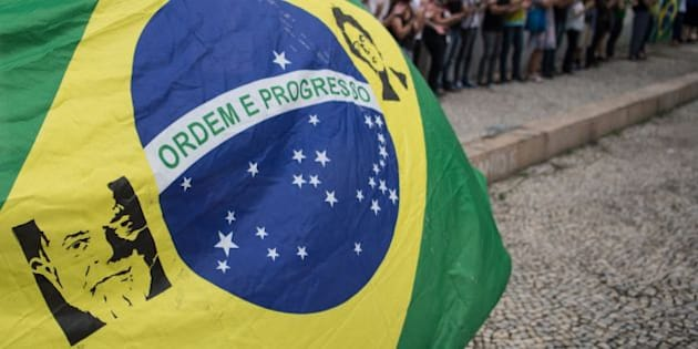 People demonstrate with a Brazilian national flag depicting the portraits of Brazilian former President (2003-2010) Luiz Inacio Lula Da Silva (L) and Brazilian suspended President Dilma Rousseff during a protest against Brazilian acting president Michel Temer in downtown Rio de Janeiro, Brazil on May 16, 2016. Temer vowed Friday to get Latin America's largest economy back on track after a cascade of crises put an end to 13 years of leftist rule. Impeachment trial was opened Thursday in Brasilia against suspended leftist president Dilma Rousseff. / AFP / CHRISTOPHE SIMON        (Photo credit should read CHRISTOPHE SIMON/AFP/Getty Images)