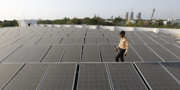 An Indian security man walks amid rooftop solar plant at the secretariat gymkhana in Gandhinagar, India, Tuesday, May 17, 2016. (AP Photo/Ajit Solanki)