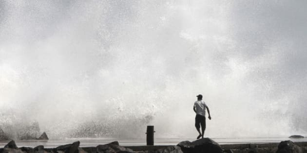 A man watches a large wave during high tide at a fishing harbour in Chennai December 28, 2011. The coastal districts in the state have been put on high alert in view of Cyclone Thane which is currently 350 km off the coast of Chennai and is likely to cross the coast on December 30, local media reported. REUTERS/Babu (INDIA - Tags: ENVIRONMENT)