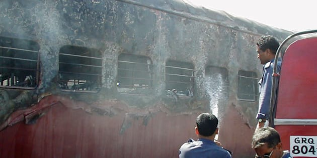 Indian firemen try to put out a fire in a train in Godhra, in the western Indian state of Gujarat February 27, 2002. Up to 56 people have died after a train carrying Hindu activists from the controversial site of a razed mosque was set on fire in western India, officials said. REUTERS/Str  JSG/CP