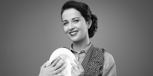 Smiling vintage housewife drying and polishing a dish with a cloth
