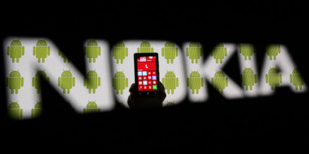 A man holding a Nokia Lumia 820 phone is seen through a Nokia logo with a background displaying Android logos on a LCD screen in the central Bosnian town of Zenica in this photo illustration taken February 25, 2014. REUTERS/Dado Ruvic (BOSNIA AND HERZEGOVINA - Tags: SCIENCE TECHNOLOGY RELIGION)