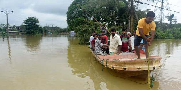 Sri Lankan residents travel by boat through the floodwaters in Pugoda, about 35 kms from capital Colombo on May 17, 2016.  Heavy rains claimed three more lives in Sri Lanka on May 17, raising weather-related deaths to 11 as more than 50,000 families were driven out of their flooded homes, officials said / AFP / ISHARA S.KODIKARA        (Photo credit should read ISHARA S.KODIKARA/AFP/Getty Images)