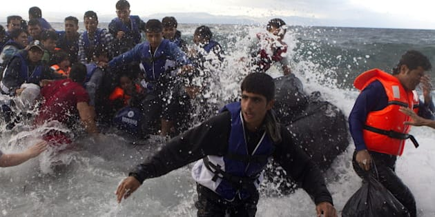 Refugees and migrants struggle to jump off an overcrowded dinghy on the Greek island of Lesbos, after crossing in rough seas from the Turkish coast, October 2, 2015. A record number of at least 430,000 refugees and migrants have taken rickety boats across the Mediterranean to Europe this year, 309,000 via Greece, according to International Organization for Migration figures. REUTERS/Dimitris Michalakis