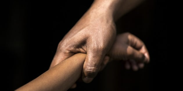 Adult holding a child's wrist