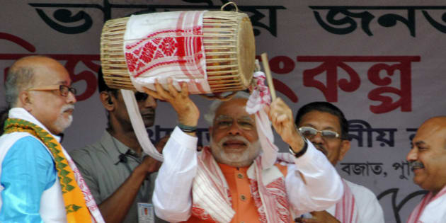 Hindu nationalist Narendra Modi (C), the prime ministerial candidate for India's main opposition Bharatiya Janata Party (BJP), plays a dhol, an Indian musical instrument, during an election campaign rally in Mangaldoi in the northeastern Indian state of Assam April 19, 2014. Around 815 million people have registered to vote in the world's biggest election - a number exceeding the population of Europe and a world record - and results of the mammoth exercise, which concludes on May 12, are due on May 16. REUTERS/Stringer  (INDIA - Tags: POLITICS ELECTIONS)