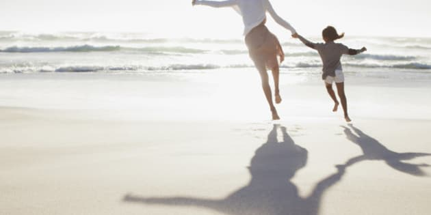 Mother and daughter holding hands and running on sunny beach