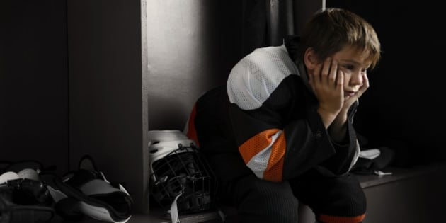 'Portrait of a male youth hockey player sitting in the dressing room tired, after the hockey game.Click on an'
