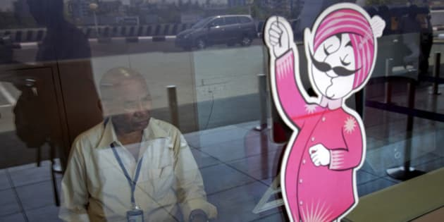 An Air India ticketing staff member sits at a closed counter in front of the Air India mascot as a passenger is reflected in the window at their ticket office at the domestic airport in Mumbai April 27, 2011. About 650 Air India pilots went on indefinite strike on Tuesday, grounding flights and causing disruptions to air travellers across the country, local media reported. REUTERS/Vivek Prakash (INDIA - Tags: TRANSPORT BUSINESS CIVIL UNREST)