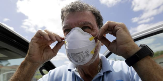 Giraldo Carratala, an inspector with the Miami-Dade County mosquito control unit, puts on a mask before spraying pesticide for mosquitoes in a residential neighborhood Tuesday, April 12, 2016, in Miami, Fla. The department was responding to complaints about mosquitoes by a resident in the neighborhood. Health officials are concerned about the spread of the Zika virus in the U.S., and they still need more money to fight the mosquitoes that spread it. (AP Photo/Lynne Sladky)