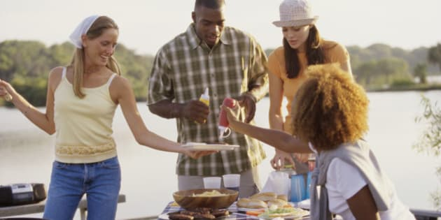 Three young women and a young man at an outdoor picnic together