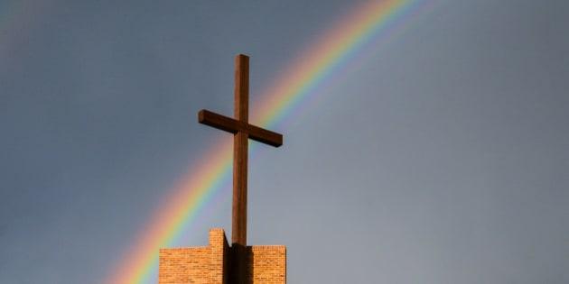Rainbow behind a cross and grey sky