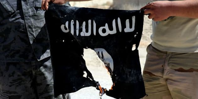 Syrian soldier sets fire on April 4, 2016 to an Islamic State (IS) group flag after Syrian troops regained control the previous day of al-Qaryatain, a town in the province of Homs in central Syria. IS jihadists withdrew from the town a week after the Russian-backed army and allied militia scored a major victory in the ancient city of Palmyra, which is also located in the vast province of Homs. The recapture of al-Qaryatain allows the army to secure its grip over Palmyra, where jihadists destroyed ancient temples during their 10-month rule and executed 280 people.  / AFP / JOSEPH EID        (Photo credit should read JOSEPH EID/AFP/Getty Images)