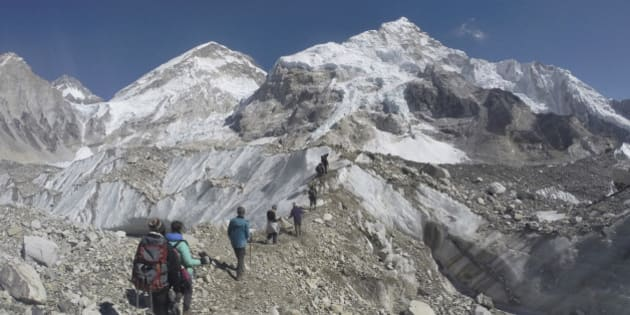 In this Monday, Feb. 22, 2016 photo, international trekkers pass through a glacier at the Mount Everest base camp, Nepal. Nepal has extended the permits of climbers who were unable to climb Mount Everest last year due to an earthquake-triggered avalanche that killed 19 people at a base camp in hopes of bringing back western climbers to the world's highest peak. Mountaineering Department official Gyanendra Shrestha said Tuesday, March 1 that the climbers can attempt to climb the world's tallest peak this year or next year without paying new fees. (AP Photo/Tashi Sherpa)