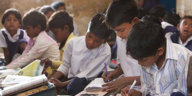 Indian schoolchildren doing their schoolwork in the classroom at their poor village school outside Bandhavgarh National Park. Children of all ages sit on the floor to do their lessons.