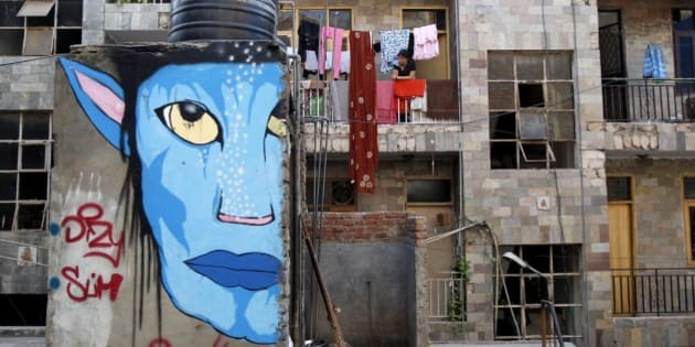 A woman looks out from the balcony of her house, as a street-art resembling a character from the Hollywood film 'Avatar' is seen on a wall in New Delhi, India, Saturday, March 31, 2012. Artists from diverse backgrounds have contributed in the street art festival aimed at building a creative movement in the New Delhi neighborhood. (AP Photo/Tsering Topgyal)