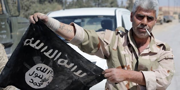 A Syrian soldier displays on April 4, 2016 an Islamic State (IS) group flag after Syrian troops regained control the previous day of al-Qaryatain, a town in the province of Homs in central Syria.