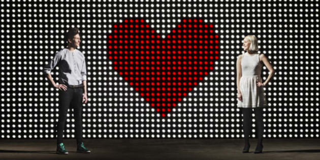young couple in front of light wall, with huge heart made of red dots, dating