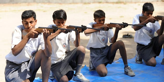 Volunteers of Bajrang Dal participate in the air rifle training session at a youth camp on the outskirts of Ahmedabad in the early morning of May 17, 2012.  Some 168 students, 18 instructors and 15 organisers are participating in a Bajrang Dal Basic Youth Camp from May 13 - 20.  Bajrang Dal, a hardline Hindu organization in India, is the youth wing of the Vishwa Hindu Parishad (VHP) and is based on the ideology of Hindutva. Apart from safeguarding 'holy cows', other goals include protecting India's Hindu identity from the perceived dangers of communalism, Muslim demographic growth and Christian conversion.   AFP PHOTO / Sam PANTHAKY        (Photo credit should read SAM PANTHAKY/AFP/GettyImages)