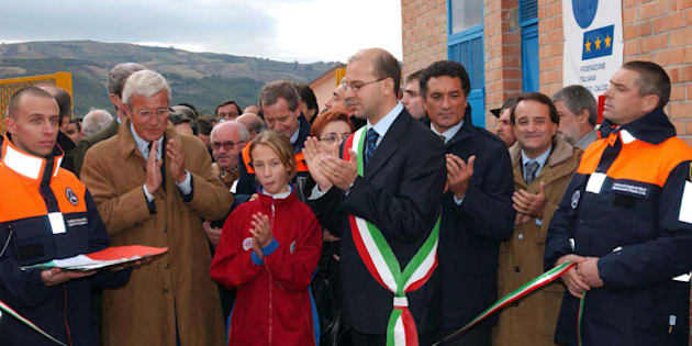 From left, Italy's national soccer team coach Marcello Lippi, in brown coat, Civil Protection Chief Guido Bertolaso, behind girl in red, new mayor of San Giuliano di Puglia Luigi Barbieri, and Claudio Gentile applaud during the inauguration of a soccer field in San Giuliano, southern Italy, Tuesday, Nov. 9, 2004. In October 2002 an earthquake hit San Giuliano, causing a school roof to collapse killing 27 children and their teacher. (AP Photo/Giuseppe Terrigno)