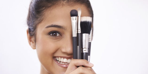 A young woman holding makeup brushes against her face