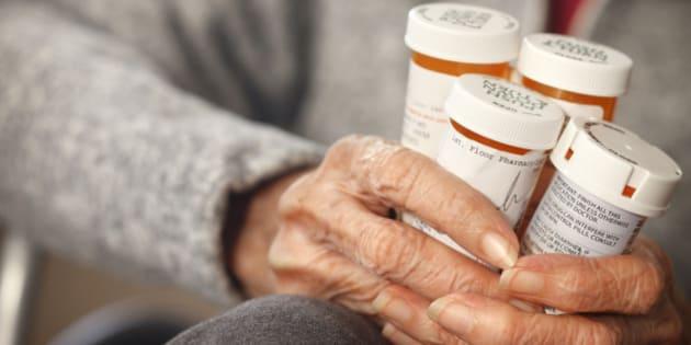 Senior citizen female holding bottles of prescription medicine sitting in a wheelchair.