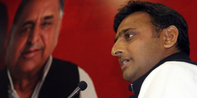 Akhilesh Yadav, the chief minister-designate of the northern Indian state of Uttar Pradesh and state party president speaks in front of a portrait of his father and the Samajwadi Party President Mulayam Singh Yadav, during a meeting with the newly elected legislators at party headquarters in the northern Indian city of Lucknow March 10, 2012. Akhilesh Yadav has won national acclaim by helping return his father to power as chief minister of Uttar Pradesh, India's most populous and politically key state where Rahul Gandhi had hoped to stage a revival for Congress as it prepares to contest national elections in 2014. REUTERS/Pawan Kumar (INDIA - Tags: POLITICS)