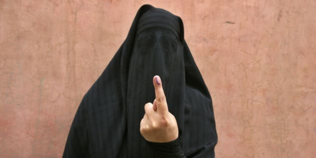 A veiled Muslim woman shows her ink-marked finger after voting outside a polling station in Doda district, north of Jammu, April 17, 2014. Around 815 million people have registered to vote in the world's biggest election - a number exceeding the population of Europe and a world record - and results of the mammoth exercise, which concludes on May 12, are due on May 16. REUTERS/Mukesh Gupta (INDIAN-ADMINISTERED KASHMIR - Tags: POLITICS ELECTIONS)