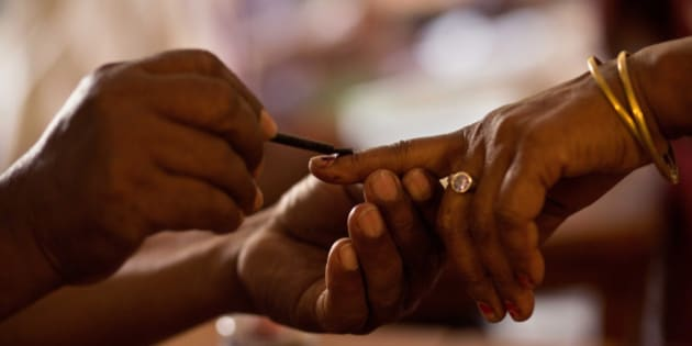 A polling official makes an ink mark on the index finger of a woman before she casts her vote during the second phase of Assam state assembly elections inside a polling station on the outskirts of Gauhati, Assam state, India, Monday, April 11, 2016. (AP Photo/ Anupam Nath)