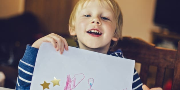 Happy smiling little boy showing a picture he has drawn.