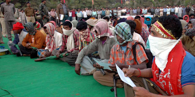Naxalites with their faces covered sit as they await to surrender before the Chief Minister of Chhatisgarh State, Dr.Raman Singh, unseen, in Raipur,India, Wednesday, Jan.3, 2007.79 Naxals surrendered according to an agency. (AP Photo)