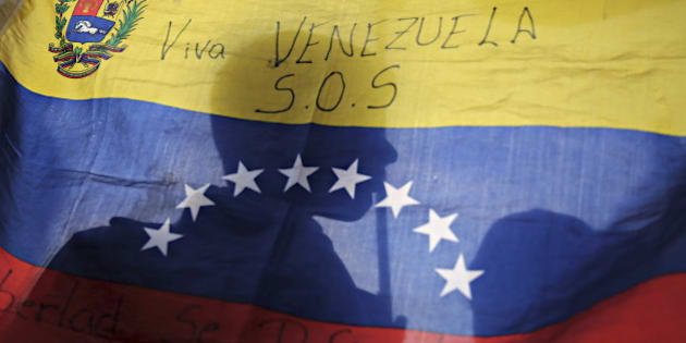 Opposition supporters are silhouetted through a Venezuelan flag during a campaign rally with candidates for the National Assembly from the Venezuelan coalition of opposition parties (MUD) in Caracas December 3, 2015. Polarized Venezuela heads to the polls this weekend with a punishing recession forecast to rock the ruling Socialists and propel an optimistic opposition to its first legislative majority in 16 years. REUTERS/Nacho Doce