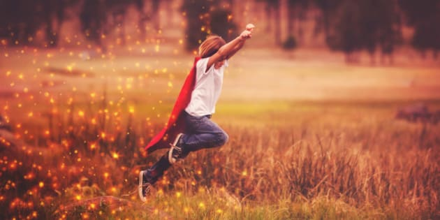 Little boy wearing a cape jumping from a rock.  Magic glitter around cape.