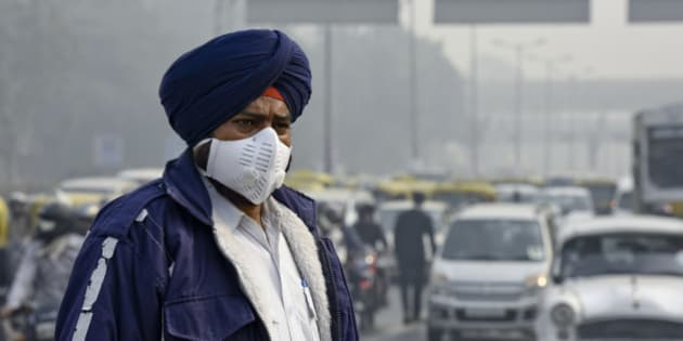 NEW DELHI, INDIA - JANUARY 4: People and traffic police wearing a mask during the implementation of odd-even vehicle formula at ITO crossing on January 4, 2016 in New Delhi, India. Contrary to apprehensions, Delhi's odd-even vehicle scheme aimed at battling pollution did not lead to the feared problems on Monday, the first full working day of the New Year. The 15-day odd-even scheme started on January 1 and aims to put odd numbered vehicles on the roads on odd dates and even numbered vehicles on even dates. (Photo by Arvind Yadav/Hindustan Times via Getty Images)