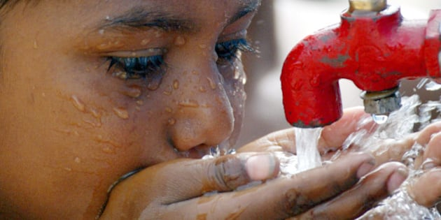A street child drinks water from a tap in a slum area of New Delhi June 4,