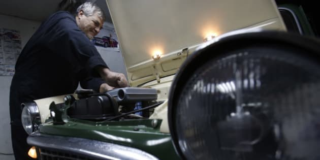 """In this file dated Friday, Nov. 28, 2014, Bosnian man Oto Novak works on a Fiat 1100 at his garage, in Bosnian town of Tuzla, 100 kms north of Sarajevo. Novak, 63, spends his retirement days restoring his 1959 Fiat 1100 with spare parts he buys on the internet. Despite their high price for his 300 euro Bosnian pension, Novak still pursues his life-long passion, fixing up this old timer car which has taken three years so far. """"My first word as a baby was """"car"""". My mum rode a motorcycle when she was seven month pregnant. Dad was a car mechanic. This love for cars must be genetic,"""" he laughs.  (AP Photo/Amel Emric)"""