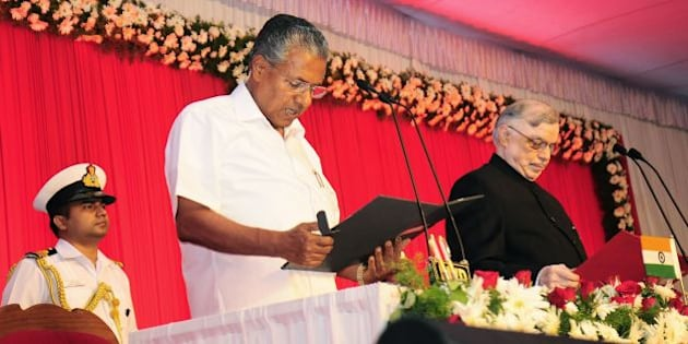 Incoming Chief Minister of the southern Indian state of Kerala Pinarayi Vijayan (C) stands alongside Governor of Kerala P. Sathasivam(R)as he takes part in a swearing-in ceremony in Thiruvananthapuram on May 25, 2016.   / AFP / STR        (Photo credit should read STR/AFP/Getty Images)
