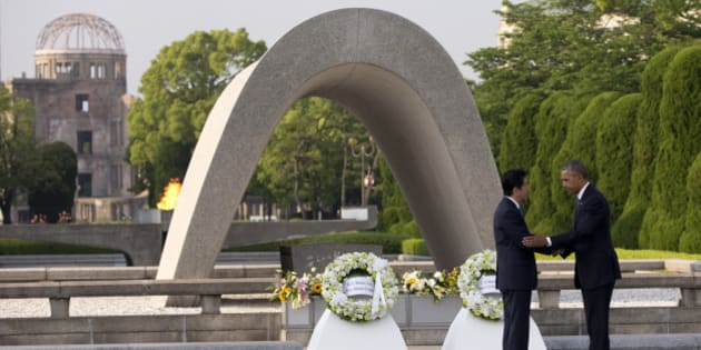 U.S. President Barack Obama, right, and Japanese Prime Minister Shinzo Abe shake hands during a wreath laying ceremony at the cenotaph at Hiroshima Peace Memorial Park in Hiroshima, western, Japan, Friday, May 27, 2016. Obama on Friday became the first sitting U.S. president to visit the site of the world's first atomic bomb attack, bringing global attention both to survivors and to his unfulfilled vision of a world without nuclear weapons. Atomic Bomb Dome is seen in the background. (AP Photo/Carolyn Kaster)