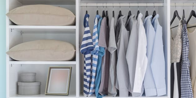 clothes hanging in white wardrobe with pillows and boxes