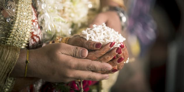 This is a Ritual in the Hindu Weddings, where 'puffed Maize gains'(Khoi) are given to the Fire God by the bride and Groom. The Fire God is considered the Witness to the marriage and is worshiped during the Marriage Rituals.Here you can see the hands of the bride and groom ready to make the offering to the Fire God.