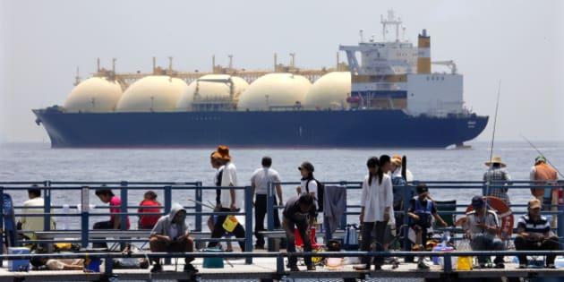 JAPAN - JUNE 20:  A liquefied-natural-gas (LNG) tanker, leaves a berth as holidaymakers fish on a pier in Yokohama City, Kanagawa Prefecture, Japan, on Saturday, June 20, 2009. The world LNG market is likely to face supply shortages around 2013 as new projects fail to keep pace with supply, according to Wood Mackenzie, a U.K. energy research and consulting company.  (Photo by Kimimasa Mayama/Bloomberg via Getty Images)